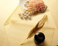 Envelope feather and pearl blank with inkwell Royalty Free Stock Photo