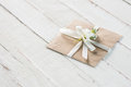 Envelope with flower and ribbon on white wooden tabletop