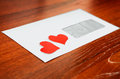 Envelope with a heart shapes on the wooden background Royalty Free Stock Image