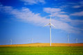 Eolian energy park with blue sky and green grass Royalty Free Stock Image