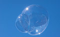 Ephemeral bubble large blown soap floating on the wind with blue sky in the background Royalty Free Stock Image