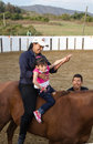 Equine therapy exhibition of for child with muscular disorder horse therapist and helpers in arena Royalty Free Stock Photos