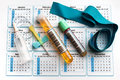 Equipment for analysis on the daily schedule blood tube urine test needle and tourniquet bottom of an appointment calendar in lab Royalty Free Stock Photo