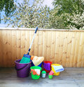 Equipment for cleaning in the house bright colourful buckets on a background of a spring garden Royalty Free Stock Images