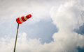 Erect red and white windsock on a pole with stripes tall post against menacing darkening sky bad weather is coming now Royalty Free Stock Image