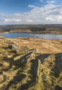 Eroded boulders on yorkshire moorland exposed and millstone grit laying a hillside overlooking a reservoir a sunny afternoon Royalty Free Stock Photography