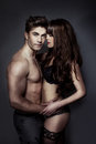 Erotic portrait of a sexy couple an attractive young posing holding each other intimately in their underwear with the women Royalty Free Stock Images