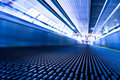 Escalator in blue corridor in trade centre Royalty Free Stock Photo