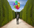 Escape businessman in the park holds the inflated balloons Royalty Free Stock Photos