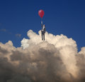 Escape businessman using a balloon flying in the clouds Royalty Free Stock Image