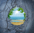 Escape city stress vacation dreaming as a dirty road pothole with the magical reflection of a tropical beach paradise scene as a Royalty Free Stock Photo