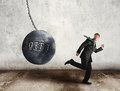 Escape the debt young businessman running away from wrecking ball as symbol of Stock Images