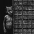 Escaping the rain little boy from after taking shower but his sad expression says it all how struggling life has been in Stock Photo