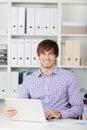 Escritório de sorriso de using laptop in do homem de negócios Foto de Stock Royalty Free