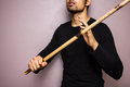 Eskrima stick fighter with rattan stick young ethnic looking man holding a as he is practicing the indigenous martial art of the Stock Photo