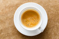 Espresso close up in white color ceramic cup on brown cloth Royalty Free Stock Photos