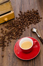 Espresso coffe in red cup with arabica beans and coffee mill Royalty Free Stock Photos
