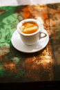 Espresso coffee cup on rustic table with sun light Royalty Free Stock Photo