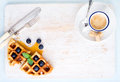 Espresso coffee cup soft belgian waffles with fresh blueberries and marple syrup on white painted wooden board over light blue Royalty Free Stock Photo