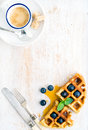 Espresso coffee cup soft belgian waffles with fresh blueberries and marple syrup on white painted wooden board over light blue Royalty Free Stock Image