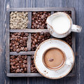Espresso cup with cream and vintage box with coffee beans Royalty Free Stock Image