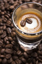 Espresso macchiato a cup of with some roasted beans background Stock Image
