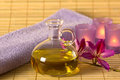 Essential oil, candles and purple towel. Royalty Free Stock Photo