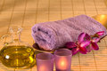 Essential oil, candles, towel and purple flowers. Royalty Free Stock Photo