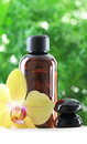 Essential oil with orchid flower and zen stones Royalty Free Stock Photo