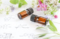 Essential oils on science sheet with herbs Royalty Free Stock Images