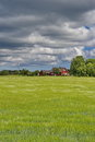 Estonian countryside green field cloudy sky and traditional rural house Stock Images