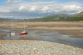 Estuary sail boats a person preparing on the sand of an at low tide with mountains in the distance Stock Photos
