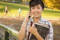 Estudante fêmea holding books e fala de raça misturada no telefone Fotos de Stock