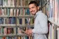 Estudante novo using his laptop em uma biblioteca Fotos de Stock Royalty Free