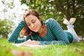 Estudante ocasional de sorriso que encontra se na grama que lê um livro Foto de Stock