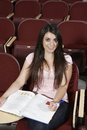 Estudiante sitting with book en sala de clase Foto de archivo