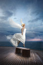 Ethereal, divine, unreal bride lfly like a bird from ocean pier. Royalty Free Stock Photo