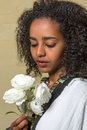 Ethiopian beauty beautiful young woman in traditional dress holding white roses Stock Image