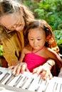 Ethnic elderly woman teach child play piano
