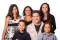 Ethnic family good looking young happy with four children and tattooed and pierced parents Stock Photo