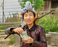 Ethnic miao hmong chinese guizhou province china april man group with a musket on his shoulder counts yuan earned at village Stock Photo