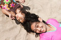 Ethnic mother and child lay down on beach sand Stock Image