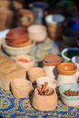 Ethnic spices cinnamon and other in wooden cups and pottery at ornament surface shallow dof Royalty Free Stock Image