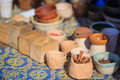 Ethnic spices and pottery cinnamon other in wooden cups at ornament surface shallow dof Stock Photos
