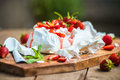 Eton mess classic british summer dessert called strawberries crushed meringue and whipped cream on wooden board Royalty Free Stock Images