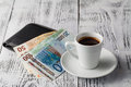 Euro bill and cup of coffee on wooden table. Payment, tip. Royalty Free Stock Photo