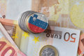 Euro coin with national flag of slovenia on the euro money banknotes background