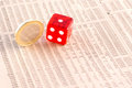 Euro coins and red dice on financial newspaper Stock Image