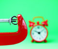 Euro under pressure a silver symbol placed in a red clamp with a pastel green background with a red alarm clock in the background Stock Images