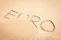 Euro written in sand on beach with sea waves starting to erase the word Royalty Free Stock Photos